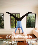 Funny pics of a Hispanic business man doing a hand stand on a white leather chair at home in his living room.